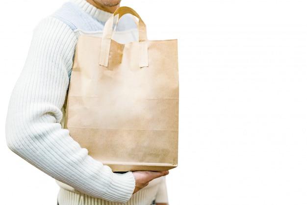 白で隔離される白いセーターで男性の手にハンドルを持つ空白の茶色の紙袋