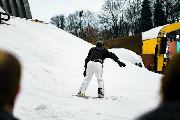 Человек в белых штанах и черный пиджак, выезжая со склона на сноуборде.