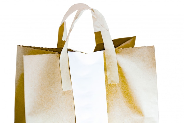 白で隔離される白い空白の領収書と茶色の紙袋