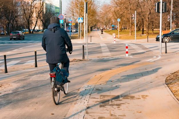 冷ややかな天気でバッグを持って街の自転車に乗って男