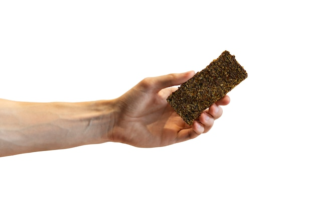 人間の手で生のシャキッとした亜麻パン。生、ビーガン、ベジタリアン料理