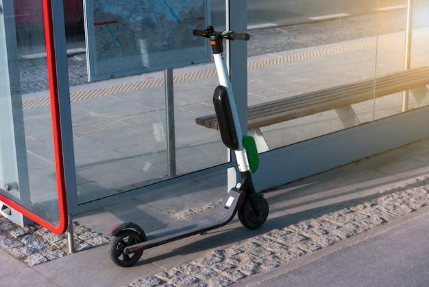 電気スクーターはダウンタウンの通りに沿って立っています。公共スクーターを借りる