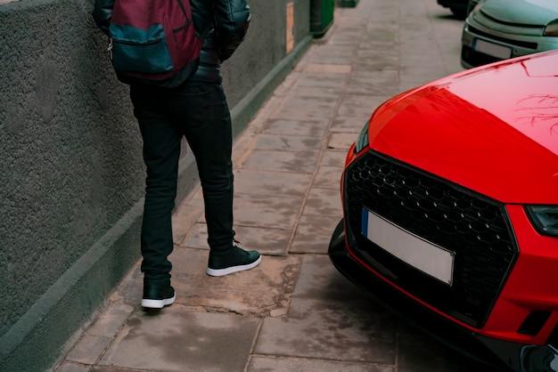 交通ルールの違反。赤い車が建物の近くに駐車している舗装の上を歩く男
