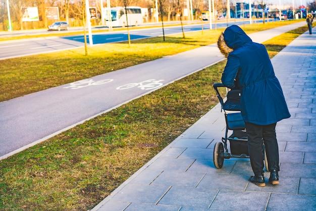 Женщина в черном пиджаке и капюшоне гуляет с коляской на тротуаре
