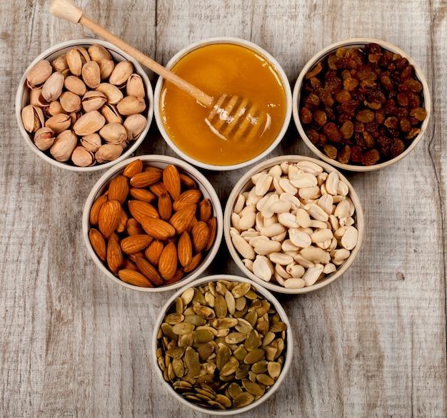 セラミックプレートのピスタチオ、アーモンド、ピーナッツ、カボチャの種、レーズン、蜂蜜。