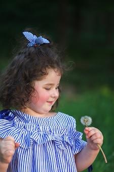 タンポポを吹く美しい巻き毛の少女。