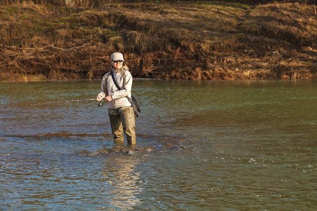 女性は川に立っている回転魚をキャッチします。
