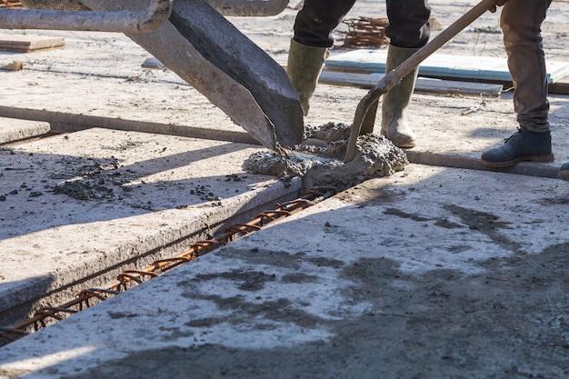 Работник заливает бетонную смесь в фундамент дома