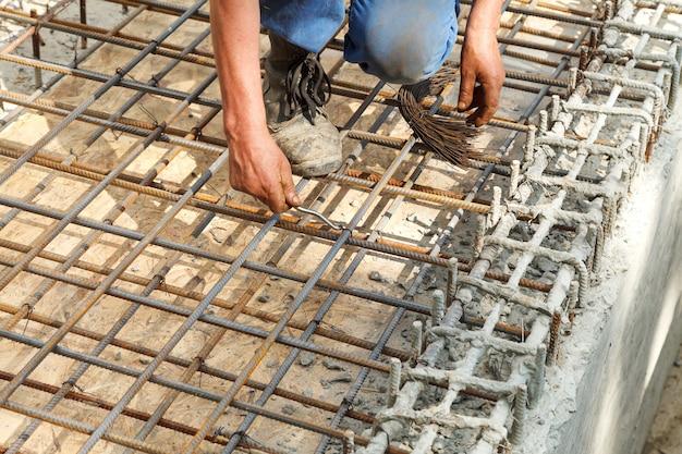 作業員は鋼鉄製の鉄筋をワイヤーで結びます。