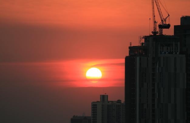 Красивое заходящее солнце над зданиями пригородов бангкока, таиланд