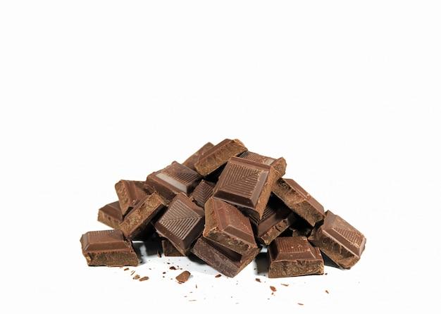 Куча темных кусочков шоколада, изолированных на белом фоне