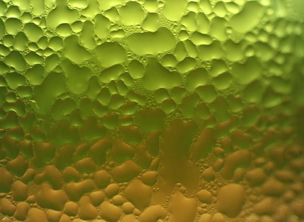 水のマクロ撮影は緑とオレンジ色のツートンカラーのガラス上のテクスチャを削除します