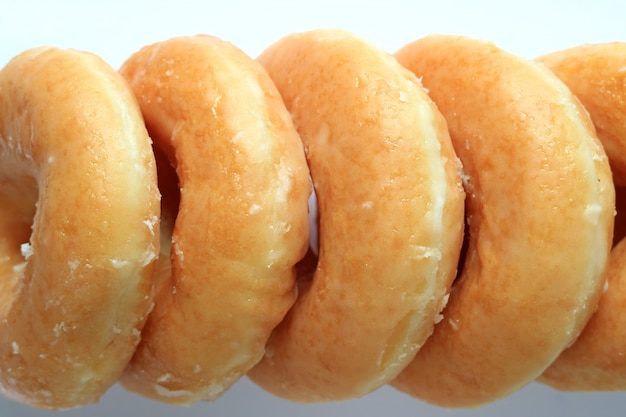 並んで砂糖艶をかけられたドーナツの質感、背景の平面図のクローズアップ