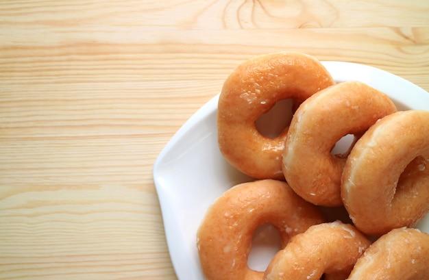 木製のテーブルの上の白い皿に砂糖艶をかけられたドーナツのトップビュー