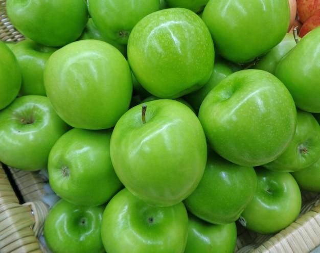 背景に引けた、バスケットの鮮やかな緑のりんごのヒープ