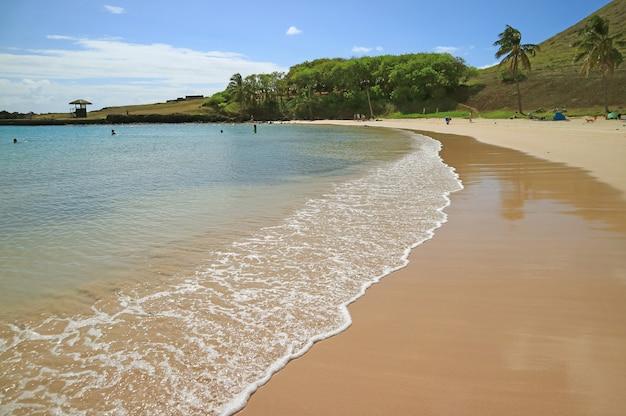 Волна из тихого океана на песчаном пляже анакена, остров пасхи, чили, южная америка