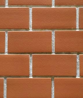 Конец-вверх покрашенной апельсином терракотовой стены кирпичей, для предпосылки, текстура