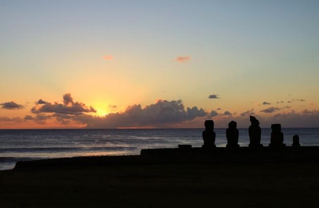 Церемониальная платформа аху тахай со статуями моаи против закатного неба, остров пасхи, чили