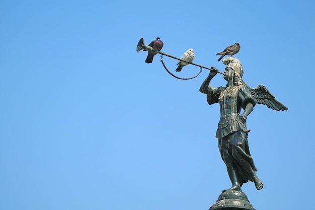Три голубя отдыхают на исторической статуе ангела славы на фонтане на площади пласа майор в лиме, перу