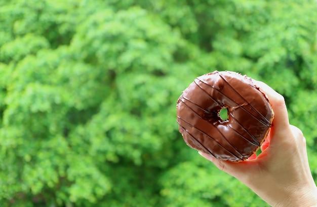 バックグラウンドでぼやけて鮮やかな緑の葉とチョコレートコーティングドーナツを持っている女性の手のクローズアップ