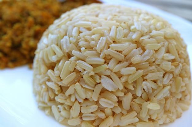 Закрытый на пару тайский коричневый рис с жасмином подается на белой тарелке