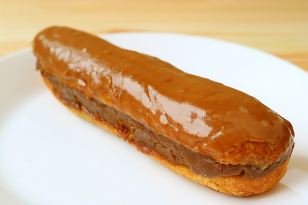 Закрыть аппетитный карамельный эклер с шоколадом на белой тарелке