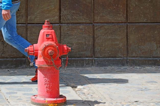 Красный огнетушитель на пешеходной дорожке с человеком, идущим позади, старый город пуно, перу, южная америка