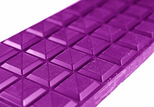 白い背景上に分離されて鮮やかな紫色のチョコレートバーで引けた