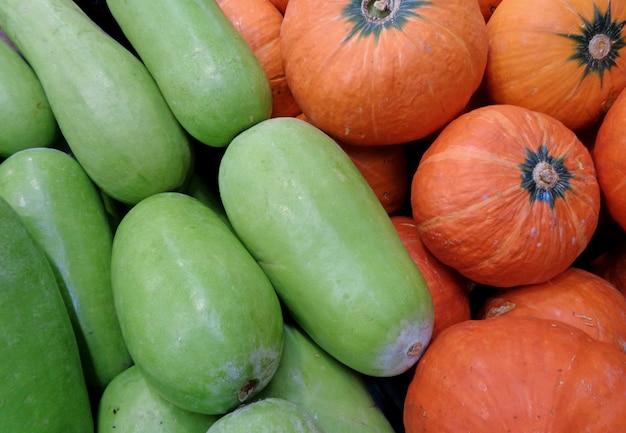 タイ市場で緑色の冬のメロンとオレンジ色のカボチャの山
