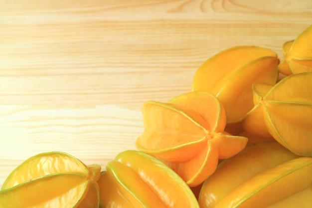 木製のテーブルに鮮やかな黄色の熟した新鮮なスターフルーツのヒープ