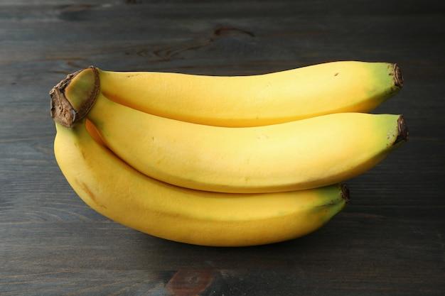暗い木製の背景に分離されたバナナの束