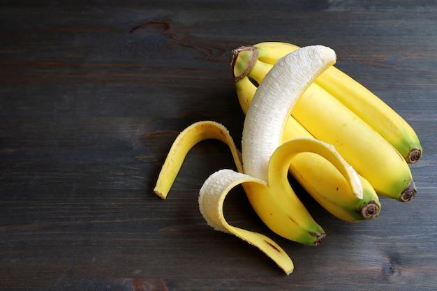 Один очищенный банан на гроздь бананов, изолированных на темно-коричневом деревянном столе