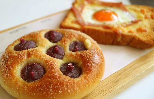ぼやけた卵とハムトーストとクローズアップ紫サツマイモクリームパン