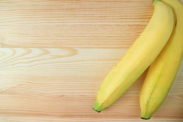 Пара желтых спелых бананов, изолированных на деревянный стол