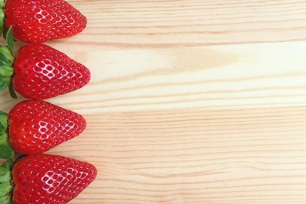 鮮やかな赤の新鮮な熟したイチゴ果実が木製のテーブルに並んで