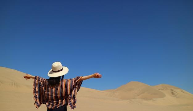Одна женщина наслаждается потрясающим видом на пустыню уакачина в регионе ика в перу