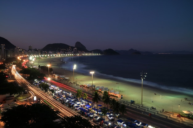 夜、リオデジャネイロ、ブラジルの距離でコパカバーナビーチとシュガーローフ山の美しい空撮