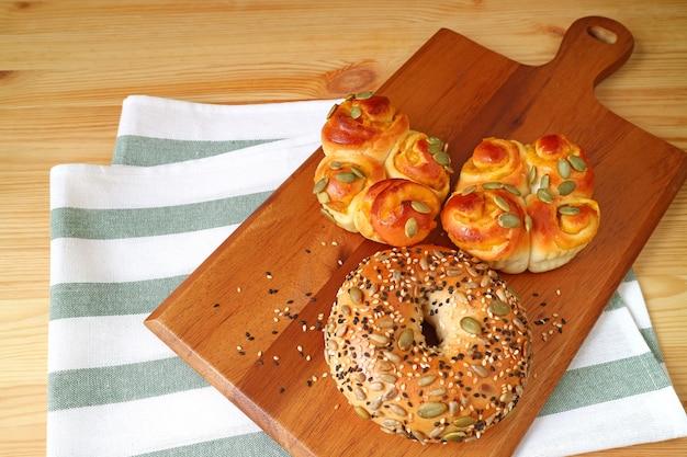 木製トレイにカボチャの種、ひまわりの種、ゴマと種類のパン