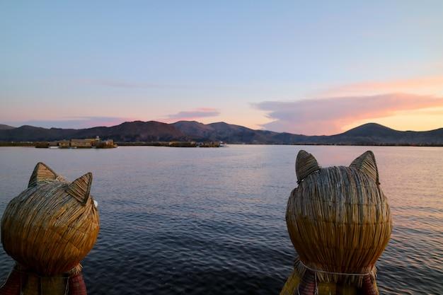 Озеро титикака после захода солнца, увиденное со знаменитой тростниковой лодки с парой носков в форме пумы, пуно, перу