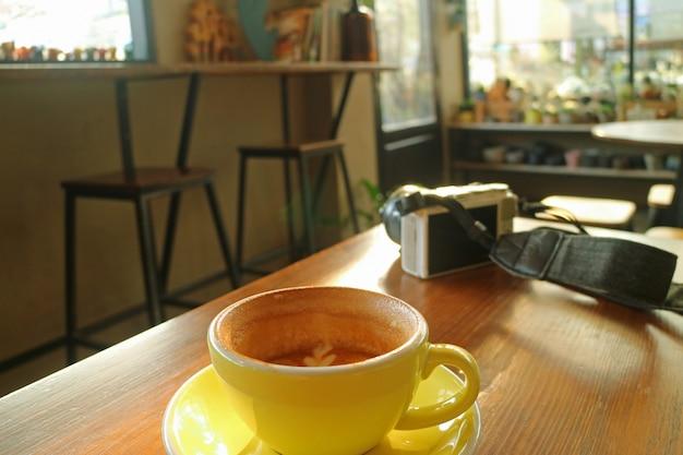 休憩時間中に白いカメラと木製のテーブルの上のカプチーノコーヒーの半分カップ