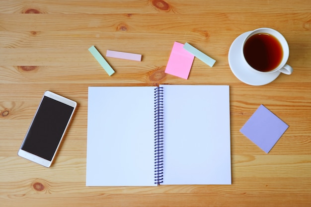 空のページが木製の作業机の上のノート、スマートフォン、メモ帳の紙と熱いお茶のカップを開いた