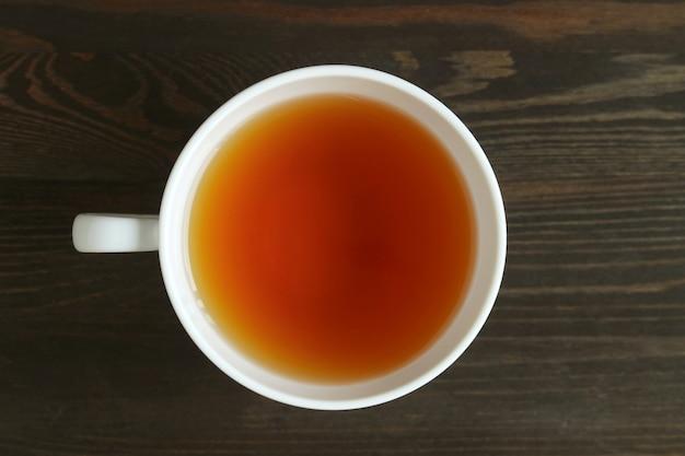 ダークブラウンの木製テーブルの上のロースト大麦茶または日本のムギチャのトップビュー