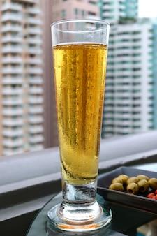 バックグラウンドでぼやけの高層ビルと、屋根の上のバーで冷たい生ビールのガラス