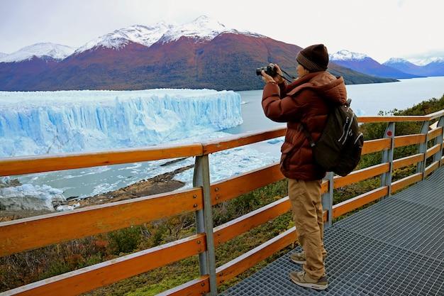 ロスグラシアレス国立公園、エルカラファテ、パタゴニア、アルゼンチンのペリトモレノ氷河の写真を撮影する人