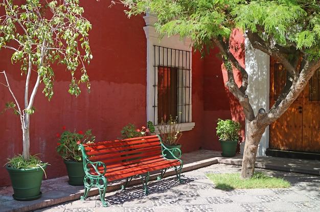 南アメリカ、ペルー、アレキパの太陽の光の庭の赤と緑のベンチ