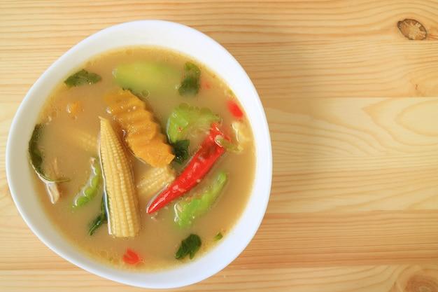 空の木製テーブルの上のタイのスパイシーなミックス野菜スープのトップビュー