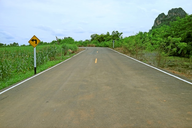 Дорожный знак левого поворота на обочине дороги в таиланде