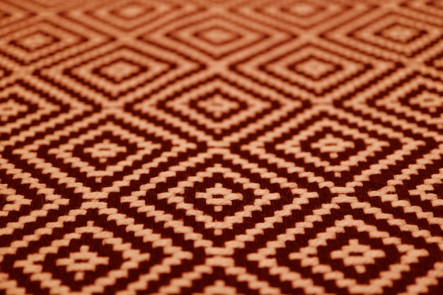 Крупный план оранжевого и темно-коричневого цвета этнической ткани