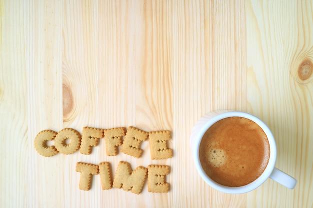 木製のテーブルの上のアルファベットビスケットと一杯のコーヒーと単語のコーヒータイムのスペルのトップビュー