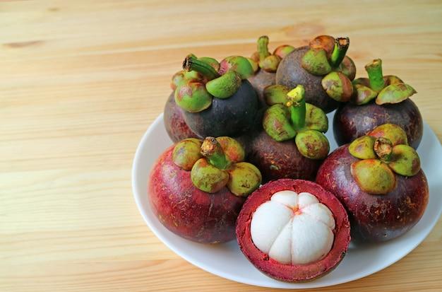 マンゴスチン全体のフルーツのプレートと木製のテーブルに美味しいピュアホワイトの肉を表示するためにオープン